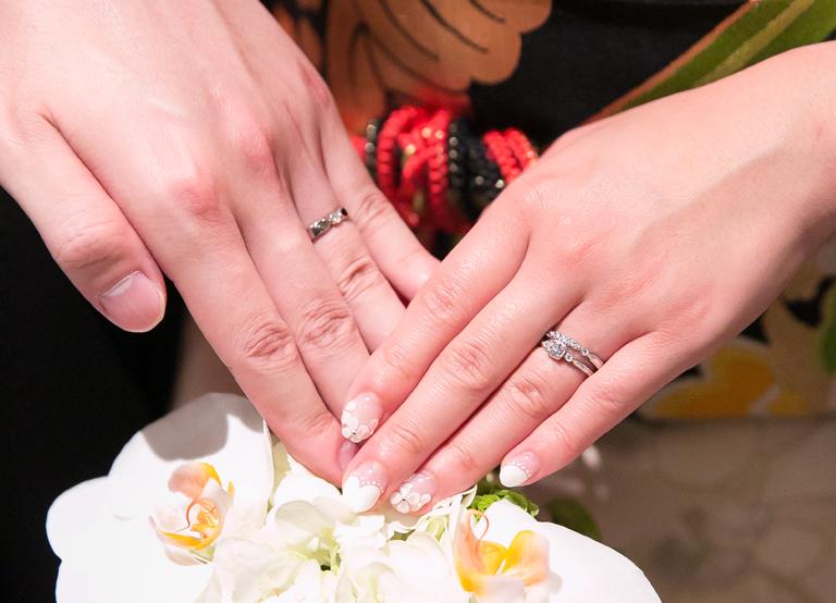 結婚式で婚約指輪・結婚指輪を重ね着けする花嫁と、結婚指輪を着ける新郎の手(パーフェクトセットリング)